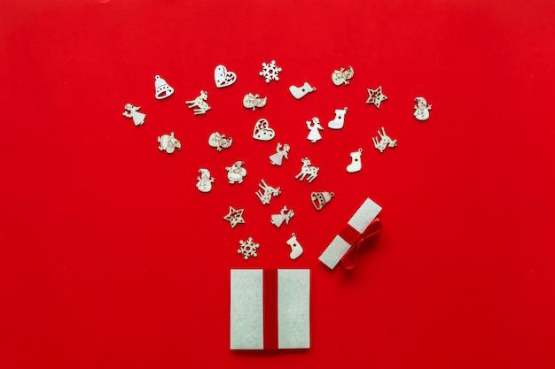 Weihnachtsgeschenke stellt papierkunst auf rotem hintergrund mit festlichen feiertagsdekorationen dar