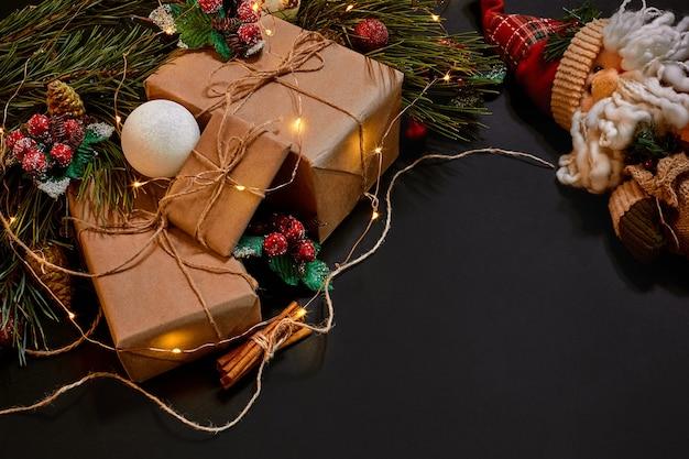 Weihnachtsgeschenke und girlande in der nähe von grünem fichtenzweig auf schwarzem hintergrund. weihnachten hintergrund. ansicht von oben. platz kopieren. stillleben. flach liegen. neujahr