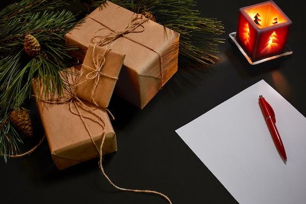 Weihnachtsgeschenke und notizbuch, die nahe grüner fichtenniederlassung auf draufsicht des schwarzen hintergrundes liegen. platz kopieren. stillleben. flach liegen. neujahr