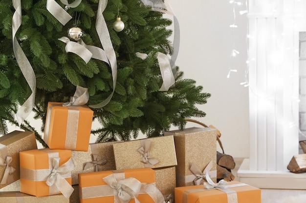 Weihnachtsgeschenke unter tanne im zimmer