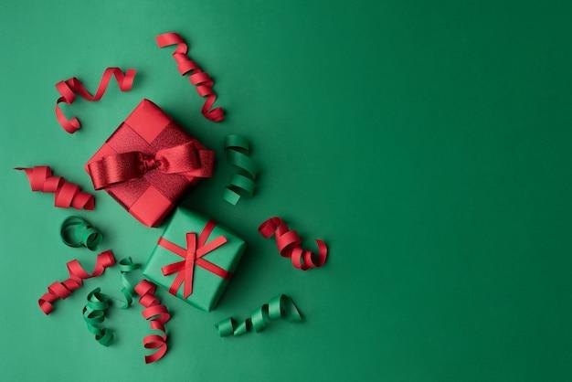 Weihnachtsgeschenke verpackt in rotem und grünem papier auf einer grünen hintergrundansicht von oben