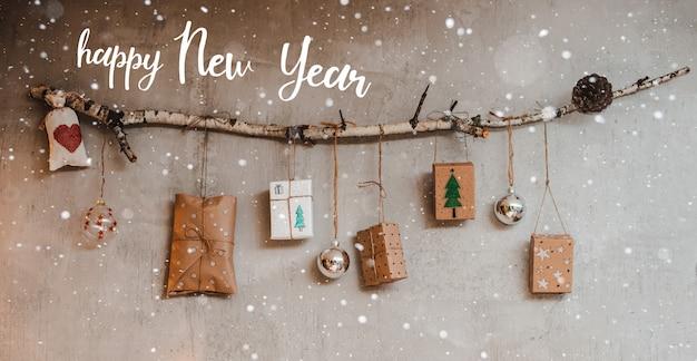 Weihnachtsgeschenke, verpackt mit kraftpapier und handgemachten dekorationen, hängen an einem seil, das an einem stock gegen eine graue betonwand gebunden ist.
