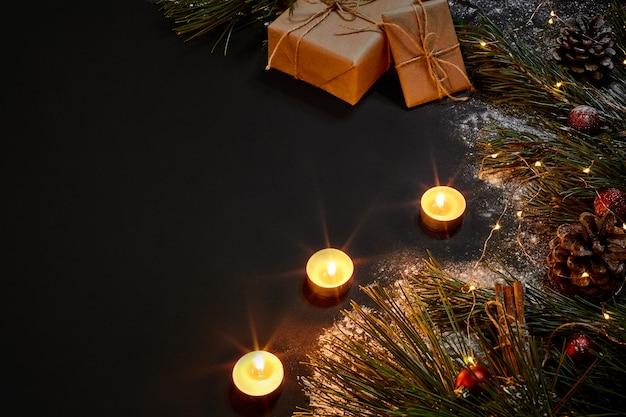 Weihnachtsgeschenke, weihnachtsbaum, kerzen, farbiges dekor, sterne, kugeln auf schwarzem hintergrund. ansicht von oben. platz kopieren. stillleben wohnung lag neujahr