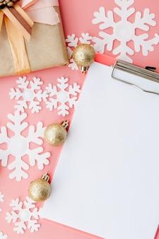 Weihnachtsgeschenke, weihnachtsverzierungen und ein offenes leeres notizbuch auf rosa. flach liegen. ansicht von oben.