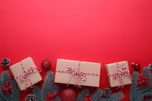 Weihnachtsgeschenkgeschenke mit roten dekorationen auf einem roten hintergrund.