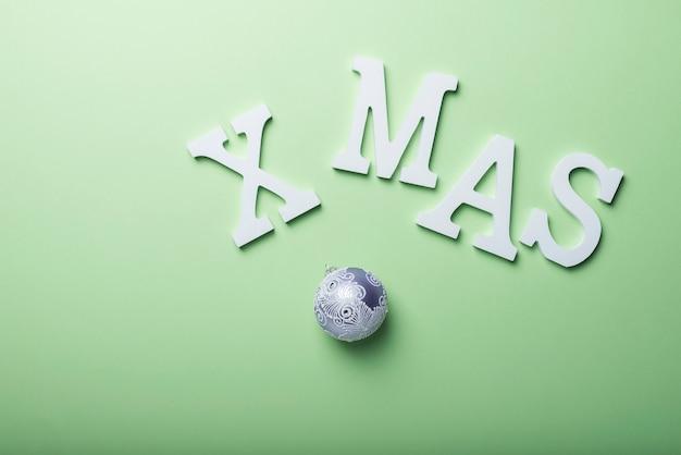 Weihnachtsgeschenkkarte mit weißen buchstaben auf dem grünen hintergrund. urlaubskonzept, ansicht von oben nach unten mit kopierraum für text