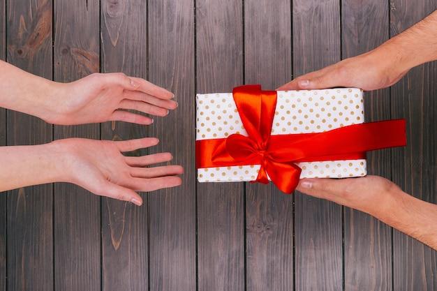 Weihnachtsgeschenkkasten von händen zu händen gegeben