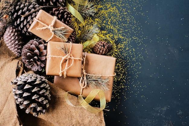 Weihnachtsgeschenkpakete und glitzernde tannenzapfen in einem festlichen und kopienraumbild