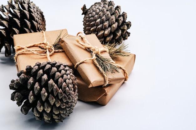 Weihnachtsgeschenkpakete und tannenzapfen auf weißem hintergrund