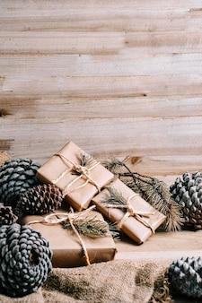 Weihnachtsgeschenkpakete und tannenzapfen mit rustikalem holzhintergrund und kopierraum