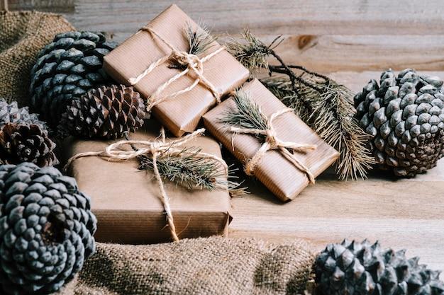 Weihnachtsgeschenkpakete und tannenzapfen mit rustikalem holzhintergrund