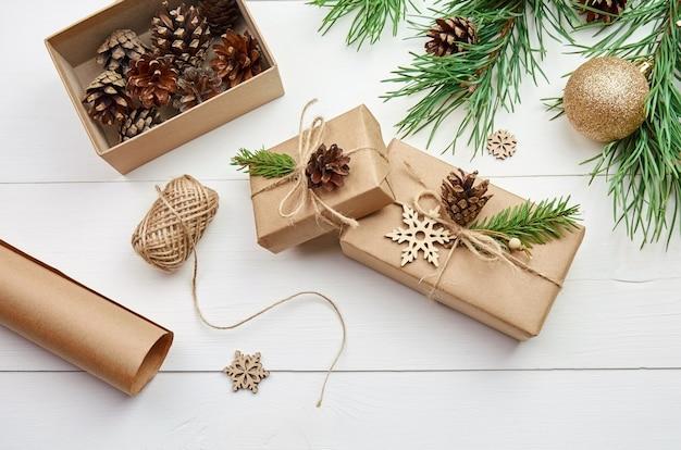Weihnachtsgeschenkverpackung und -dekoration mit festlichen kiefernzweigen auf weißem tisch