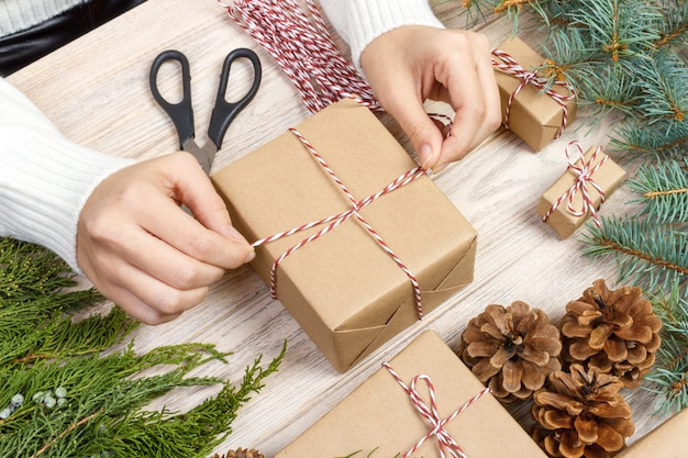 Weihnachtsgeschenkvorbereitung, geschenkbox eingewickelt im gestreiften schwarzweiss-papier, eine kiste voll kiefernkegel und weihnachtsspielwaren und verpackungsmaterialien auf einem weißen holz alt