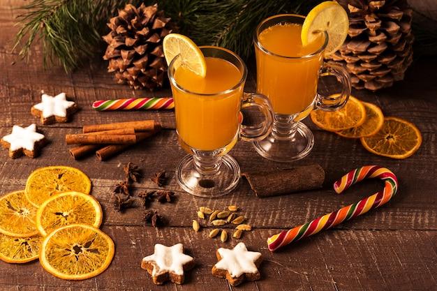 Weihnachtsgetränk und zuckerstange, kiefern, orangenchips, gewürze auf einem hölzernen brett.
