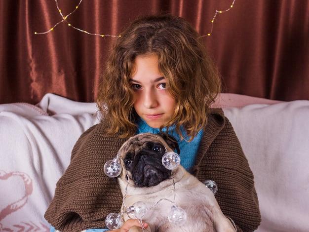Weihnachtsgirlande auf mops. charmantes mädchen mit einem sehr lustigen hund mops. gelocktes mädchen umarmt einen mops
