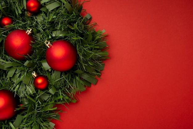 Weihnachtsgirlande aus blättern und kugeln auf einem roten tisch