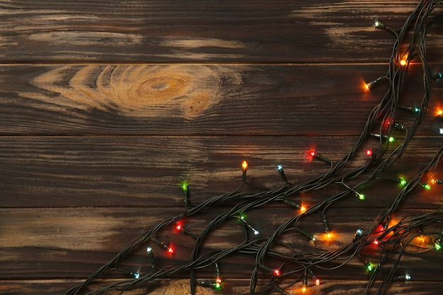 Weihnachtsgirlande beleuchtet auf braunem hölzernem hintergrund