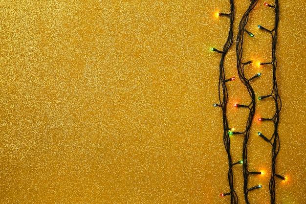 Weihnachtsgirlande beleuchtet auf goldhintergrund