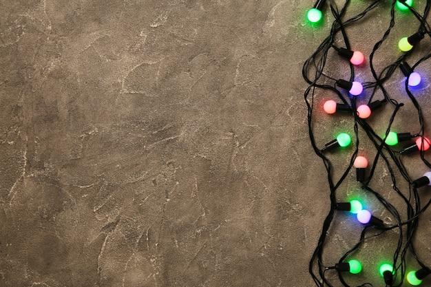 Weihnachtsgirlande beleuchtet auf grauem betonhintergrund