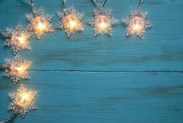 Weihnachtsgirlande lichter grenze auf einem blauen holztisch winter festliche dekoration mit kopie raum