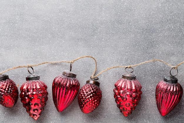 Weihnachtsgirlande mit roter kugel und grauem hintergrund.