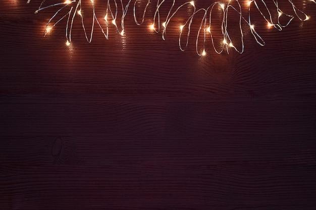 Weihnachtsgirlandenschnur mit warmen lichtern auf dunkelbraunem hintergrund