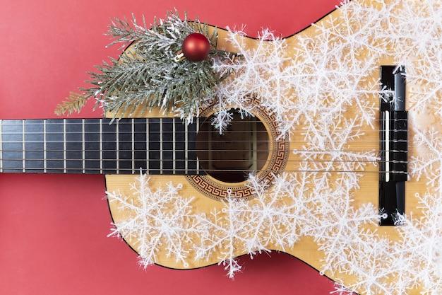 Weihnachtsgitarre auf rotem hintergrund mit schneeflocken und roten bögen. nahaufnahme des saiteninstruments. einladung zum neujahrskonzert. winterkonzert auf musikinstrumenten. kreatives hobby. anmerkungen