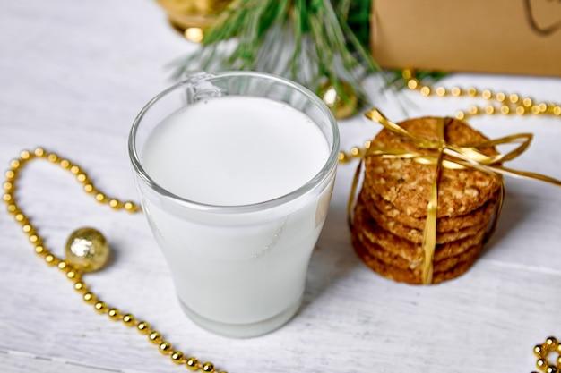 Weihnachtsglas mit milch und keksen für den weihnachtsmann auf dem tisch
