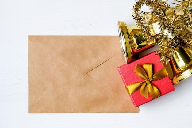 Weihnachtsglocken mit lametta und geschenk auf umschlag aus kraftpapier