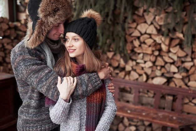 Weihnachtsglückliches paar in der liebesumarmung im kalten wald des verschneiten winters, im copyspace, in der parteifeier des neuen jahres, im feiertag und in den ferien, in der reise, in der liebe und in den beziehungen
