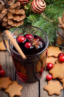 Weihnachtsglühwein. feiertagskonzept verziert mit tannenzweigen, lebkuchenplätzchen