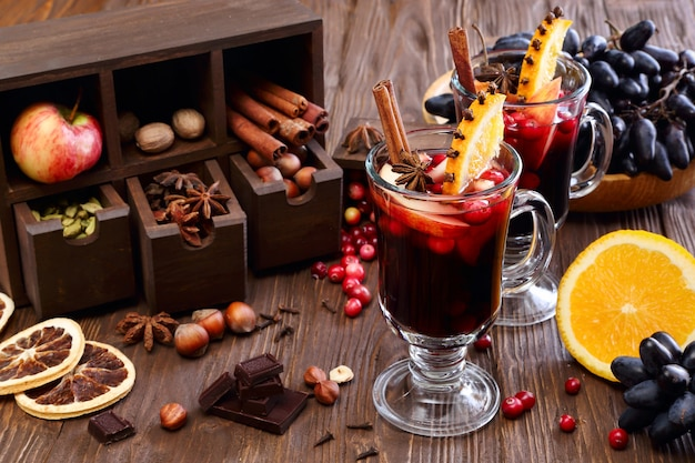 Weihnachtsglühwein mit apfel, cranberry, orange, gewürzen und schokolade auf einem holztisch