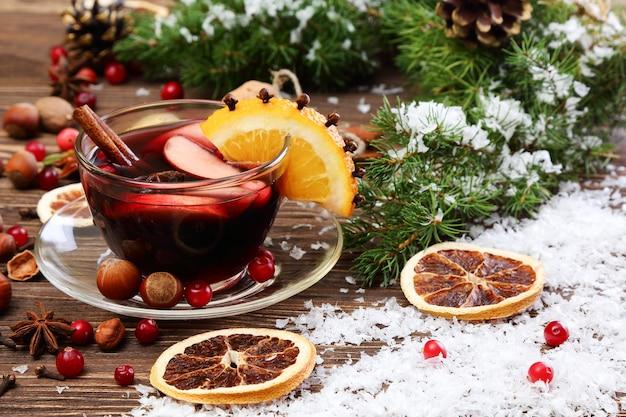 Weihnachtsglühwein mit apfel-cranberry-orange und gewürzen auf einem holztisch