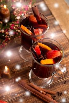 Weihnachtsglühwein mit früchten und gewürzen auf holztisch