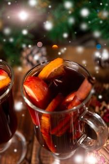 Weihnachtsglühwein mit früchten und gewürzen auf holztisch.