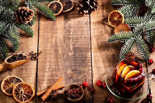 Weihnachtsglühwein mit gewürzen auf einem hölzernen rustikalen tisch