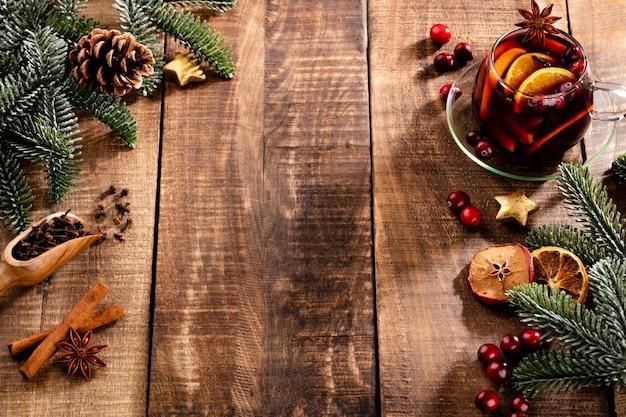 Weihnachtsglühwein mit gewürzen auf einem rustikalen holztisch.