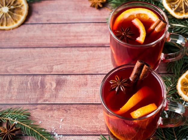 Weihnachtsglühwein mit orange und gewürzen auf holz