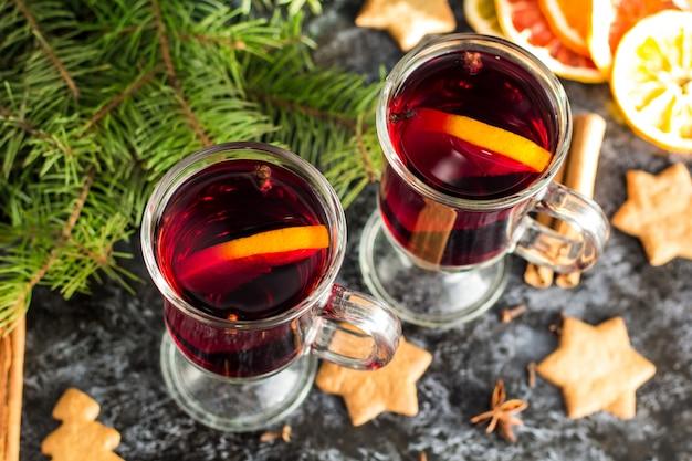 Weihnachtsglühwein mit orange zimtnelkenanis und -tannenbaum der ingwerkekse auf der dunklen tabelle