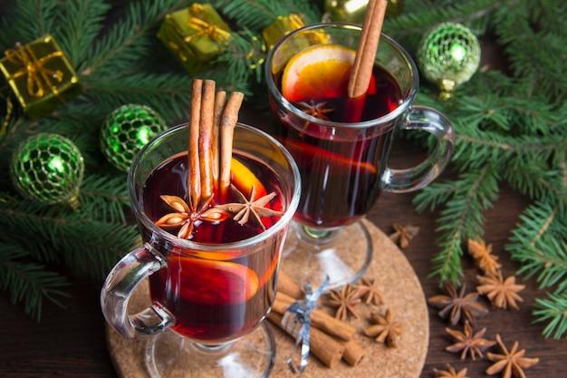 Weihnachtsglühwein mit zimt und orange. auf dem tisch liegen fichtenzweige und spielzeug