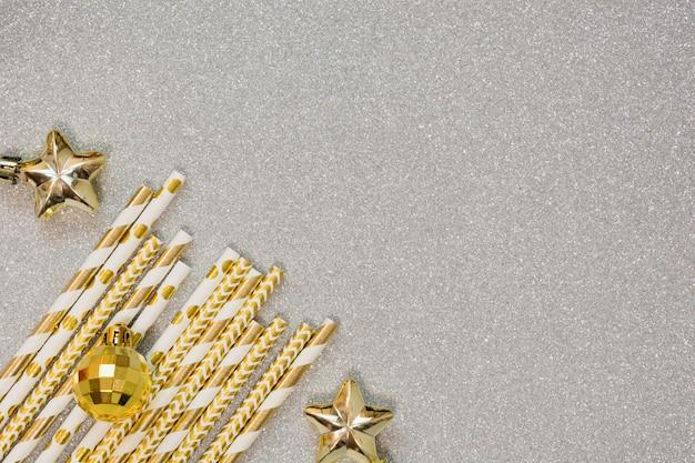 Weihnachtsgoldene bälle und trinkhalm auf silbernem hintergrund. weihnachtsfeiertags-party. flache lage, draufsicht, kopienraum. feiertagsgrußkarte.