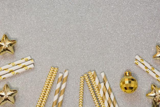 Weihnachtsgoldene bälle und trinkhalm auf silbernem hintergrund