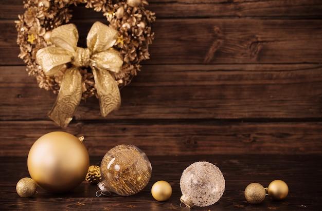 Weihnachtsgoldene kugeln und kranz auf dunklem holz