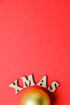 Weihnachtsgoldener ball mit aufschrift weihnachten in den hölzernen buchstaben