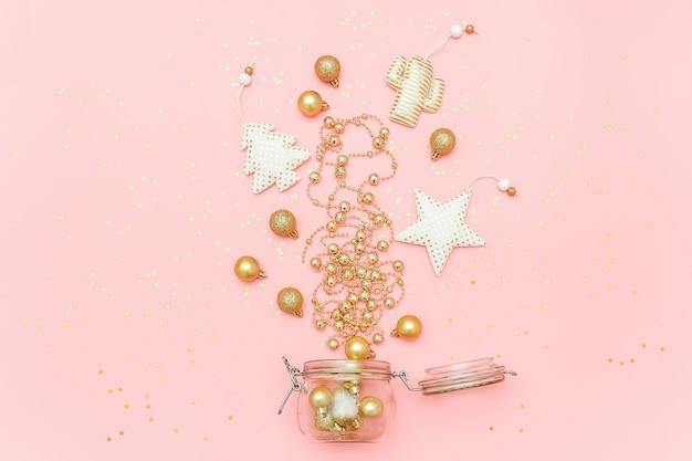 Weihnachtsgoldenes dekorationsspielzeug, girlande, flitter fliegen aus glasgefäß auf rosa karte der frohen weihnachten oder des guten rutsch ins neue jahr heraus