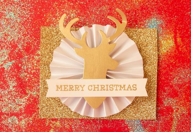 Weihnachtsgoldhirsch auf rotem hintergrund draufsicht