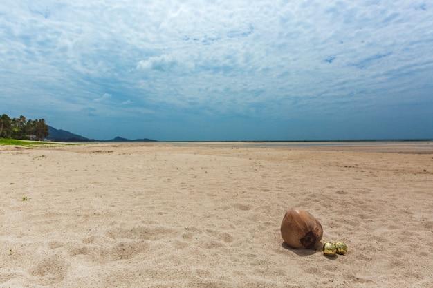 Weihnachtsgoldkugeln im sand nahe kokosnuss