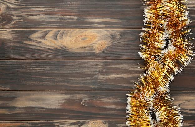 Weihnachtsgoldlametta auf braunem hölzernem hintergrund. draufsicht.