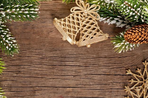 Weihnachtsgrenze aus zweig und glocken auf holzuntergrund