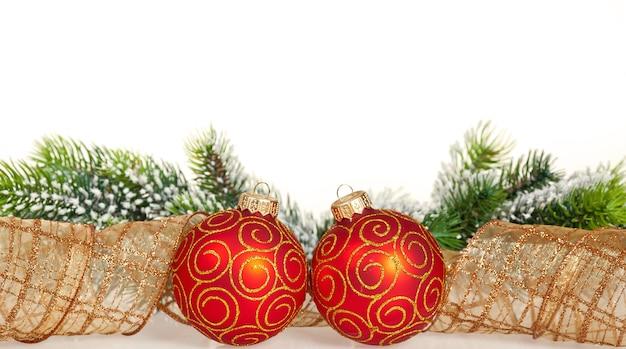 Weihnachtsgrenze aus zweig und kugeln auf weißem hintergrund